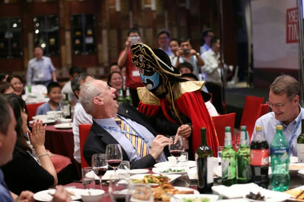 "A ""Face-Changing"" performer approaches JMP creator John Sall during the celebration dinner entertainment."