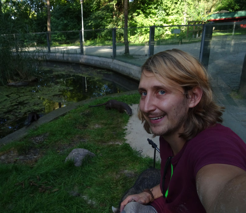 German graduate student Frederick takes a selfie with river otters.
