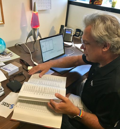 JMP developer Michael Hecht pages through The Unicode Standard 4.0 in his office. JMP recently adopted a Unicode character, the lightbulb emoji.