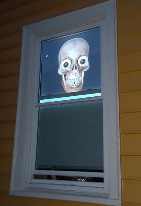 Halloween early evening, model in window